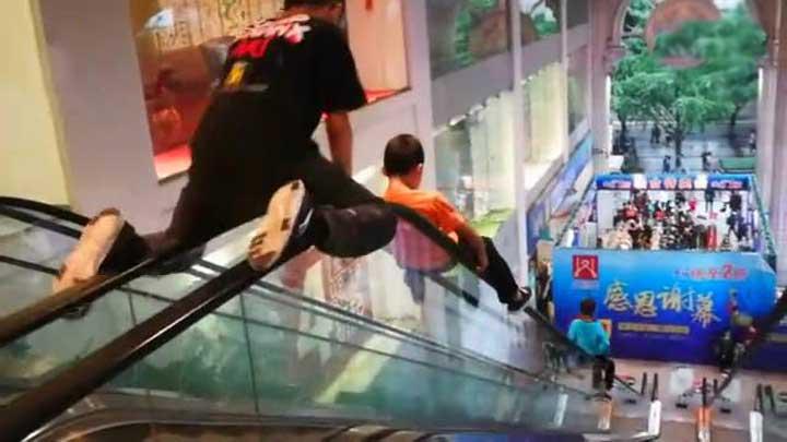 熊孩子把20米长的商场扶梯当滑梯,家长边录像边夸:真厉害