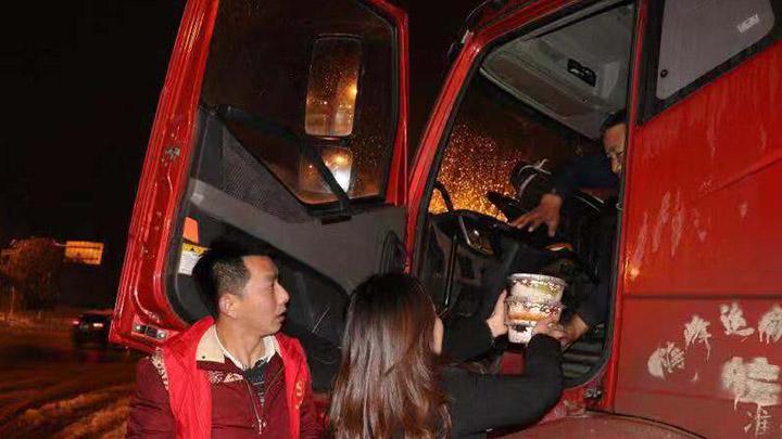 """【一城冰雪一城暖】热水、面包、牛奶……看到街道旁边的马路上有大量货车因冰雪天气滞留,长龙街道的党员干部和志愿者们为司机送上吃的喝的,社区搭建了临时的爱心驿站,为他们提供免费的食物和温暖的落脚点。<br><br>为了让滞留的司机平安度过冰雪天气,长界社区的""""新时代讲习所""""变成了临时的爱心驿站,驿站内暖风阵阵,食物充足,还有热水供应。""""怎么样?很丰盛吧?""""傍晚,在社区""""爱心驿站""""内谈笑声阵阵,戚师傅领到热气腾腾的盒饭后,迫不及待地拨通家人的视频报平安,还不忘""""炫耀""""自己丰盛的晚餐。<br><br>""""我们还专门誊出了一间房间,让他们晚上休息。""""长界社区书记郭俏告诉记者,社区还贴心地在各个路口设置了指引牌指引路过滞留的司机前往""""爱心驿站""""避寒取暖。<br>目前,还有十几位司机在爱心驿站休息。<br>"""