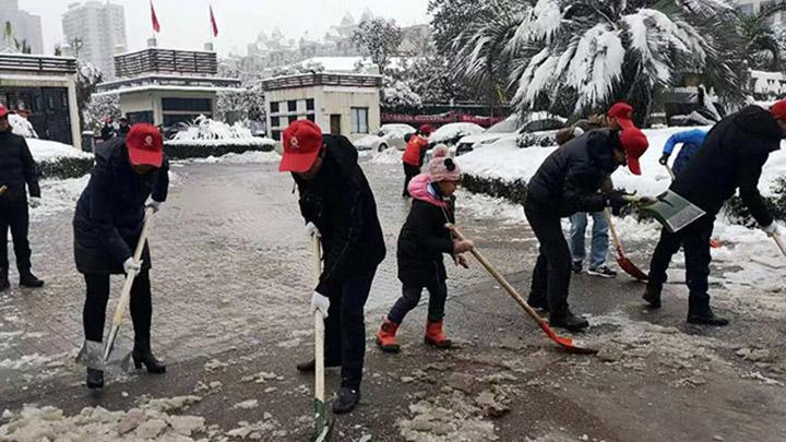 【一城冰雪一城暖】望城月亮岛街道的附近居民正在路边铲冰除雪,其中还有自发过来帮忙的小朋友。