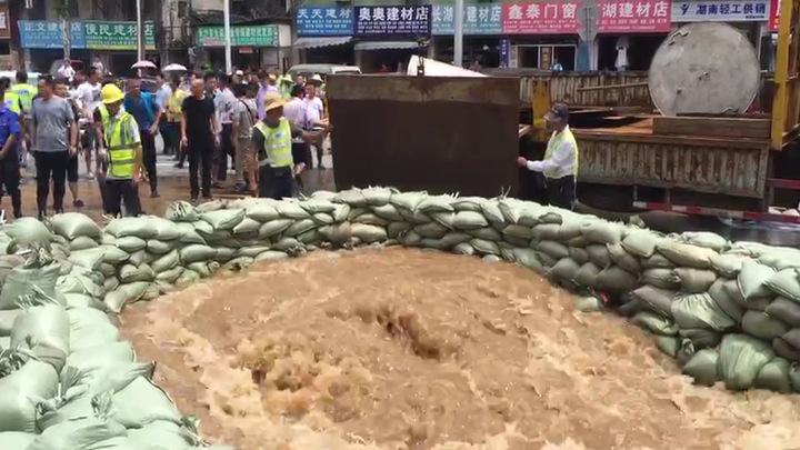 西湖路与湘江中路交汇处附近,救援人员正在用钢板堵住一处出水口