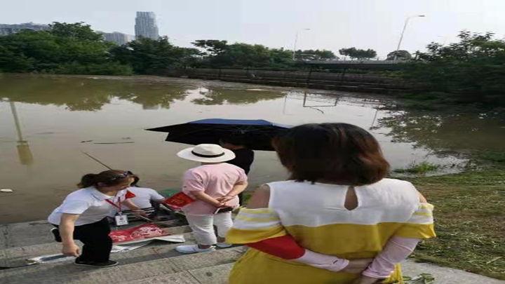 望月湖街道志愿者和工作人员劝阻在此钓鱼的市民离开。